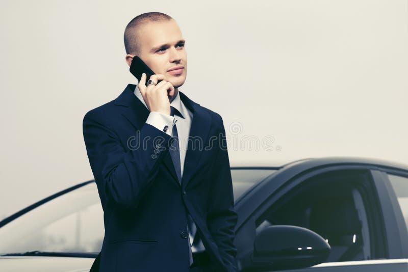 Νέος επιχειρηματίας που καλεί το τηλέφωνο κυττάρων δίπλα στο αυτοκίνητό του στοκ εικόνες
