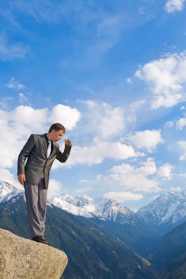 Νέος επιχειρηματίας που κοιτάζει κάτω από την κορυφή βουνών στοκ φωτογραφία