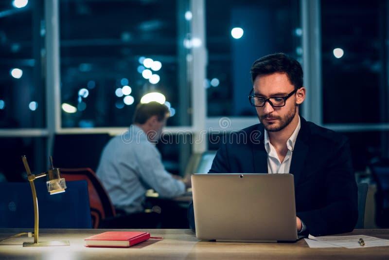 Νέος επιχειρηματίας που μένει επάνω αργά εργαζόμενος στοκ φωτογραφία με δικαίωμα ελεύθερης χρήσης