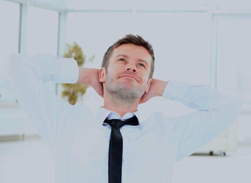 Νέος επιχειρηματίας που ονειρεύεται με τα χέρια του πίσω από την επικεφαλής συνεδρίασή του στο γραφείο στοκ εικόνες