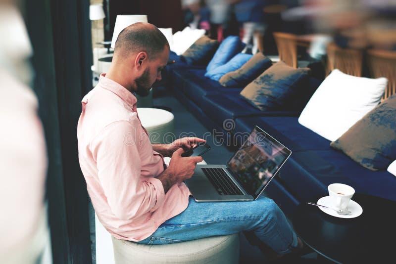 Νέος επιχειρηματίας που περιμένει το συνέταιρο του σε έναν καφέ στοκ εικόνες