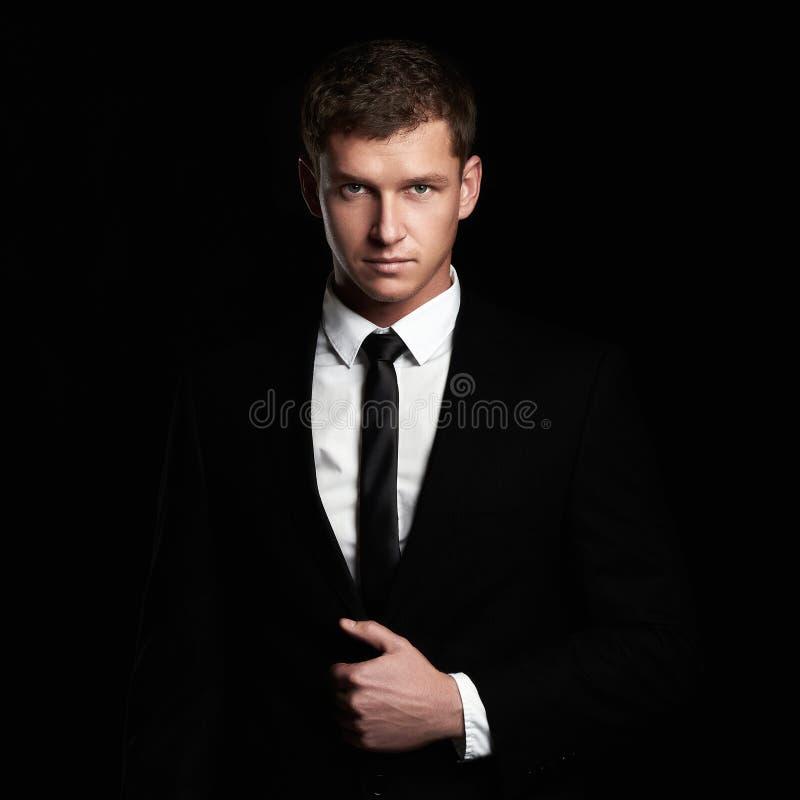 Νέος επιχειρηματίας που στέκεται στο μαύρο υπόβαθρο Όμορφο άτομο στο κοστούμι και το δεσμό στοκ φωτογραφία