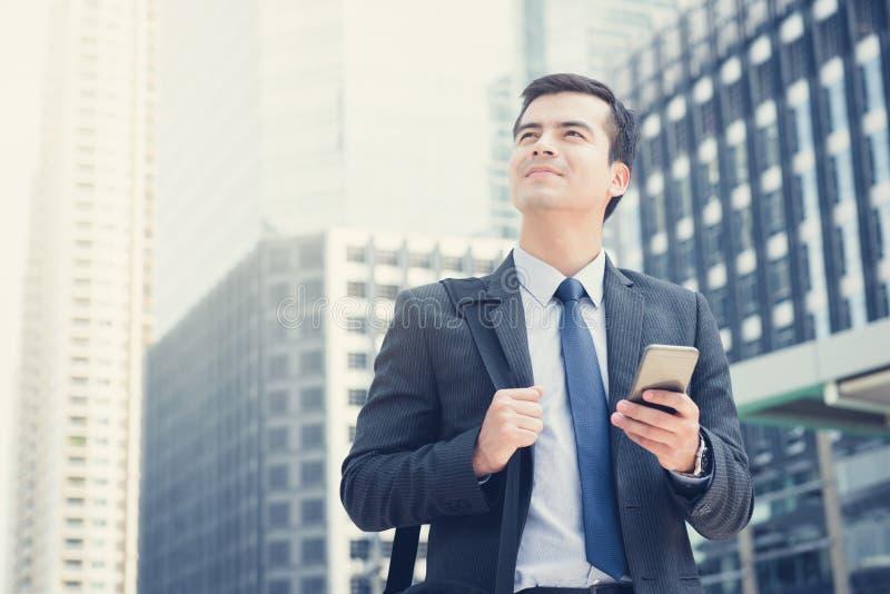 Νέος επιχειρηματίας που χρησιμοποιεί το κινητό τηλέφωνο φέρνοντας την τσάντα στην πόλη στοκ φωτογραφία