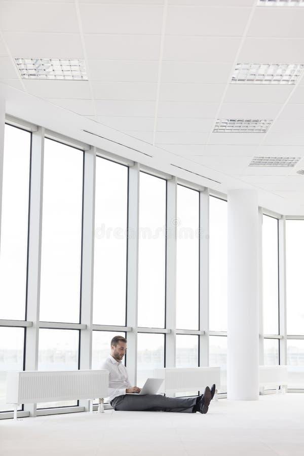 Νέος επιχειρηματίας που χρησιμοποιεί το lap-top καθμένος στη μέση των θερμαντικών σωμάτων ενάντια στο παράθυρο στο γραφείο στοκ εικόνες
