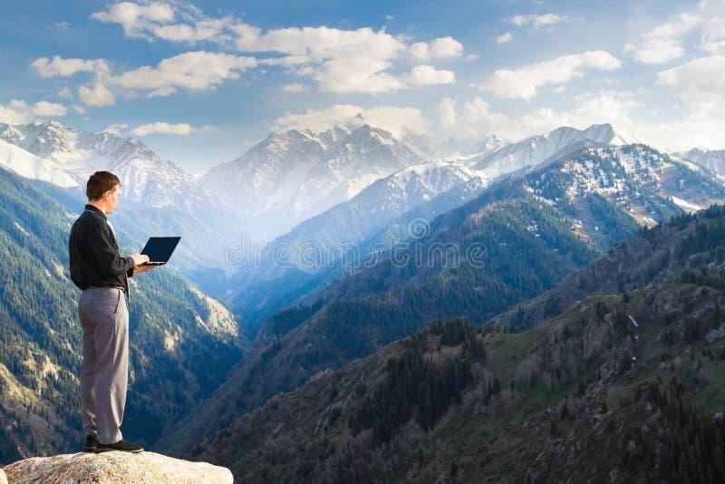 Νέος επιχειρηματίας που χρησιμοποιεί το lap-top του στην κορυφή βουνών στοκ εικόνα