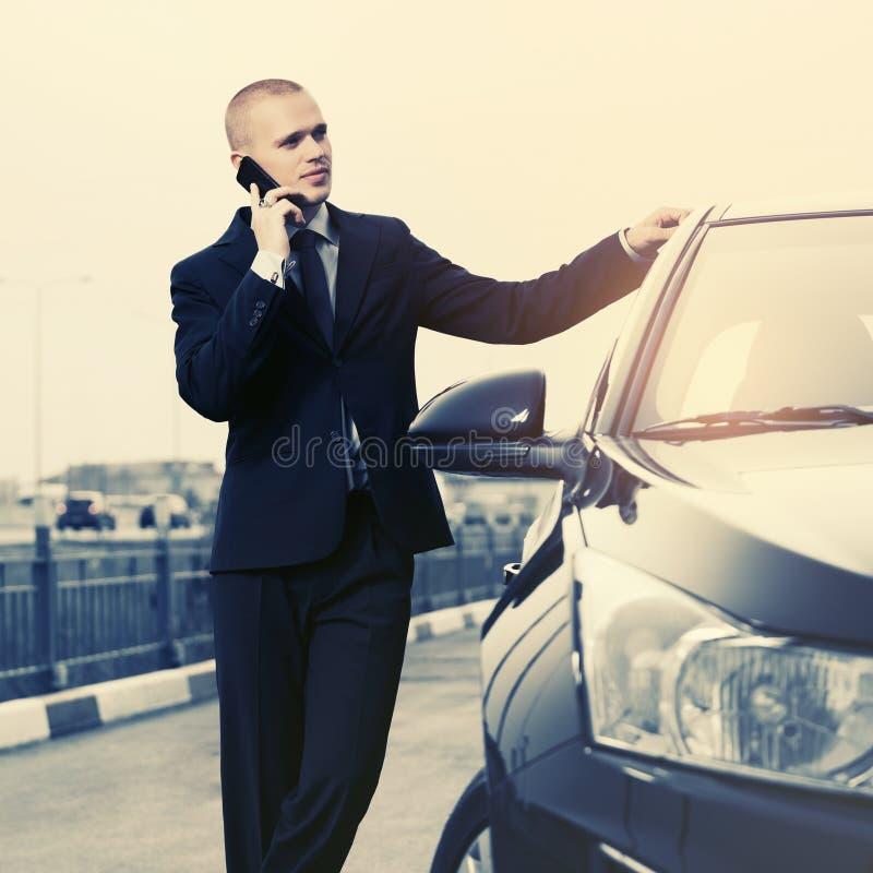 Νέος επιχειρηματίας στο σκούρο μπλε κοστούμι που καλεί το τηλέφωνο κυττάρων δίπλα στο αυτοκίνητο στοκ εικόνα με δικαίωμα ελεύθερης χρήσης