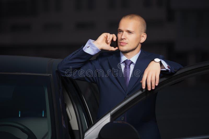 Νέος επιχειρηματίας στο σκούρο μπλε κοστούμι που καλεί το τηλέφωνο κυττάρων που κλίνει στο αυτοκίνητό του στοκ φωτογραφία με δικαίωμα ελεύθερης χρήσης