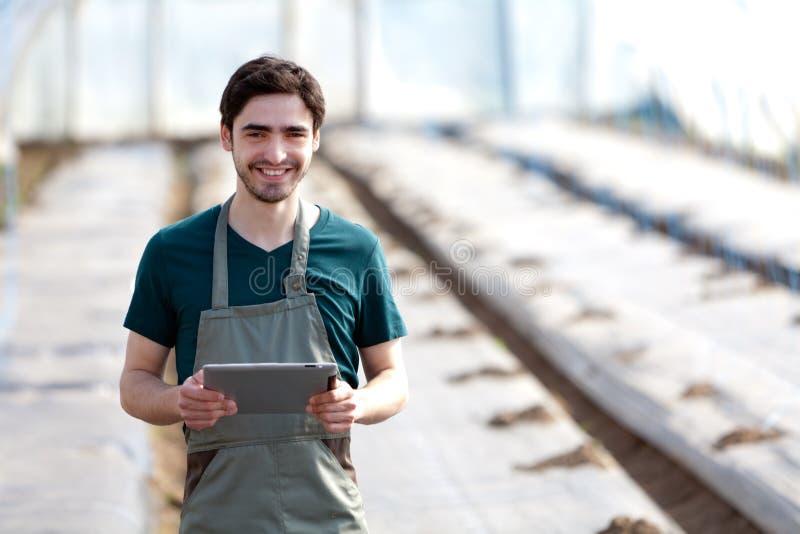 Νέος επιχειρησιακός αγρότης που εργάζεται στην ταμπλέτα του στοκ φωτογραφία