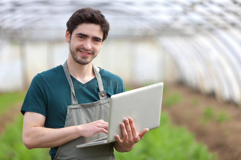 Νέος επιχειρησιακός αγρότης που εργάζεται στο lap-top του στοκ εικόνα με δικαίωμα ελεύθερης χρήσης