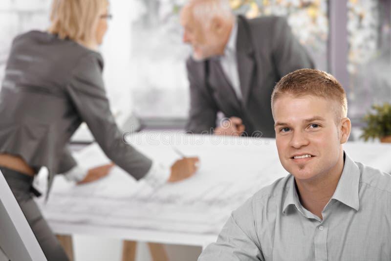 Νέος εργαζόμενος γραφείων με τους συναδέλφους στην ανασκόπηση στοκ φωτογραφία με δικαίωμα ελεύθερης χρήσης