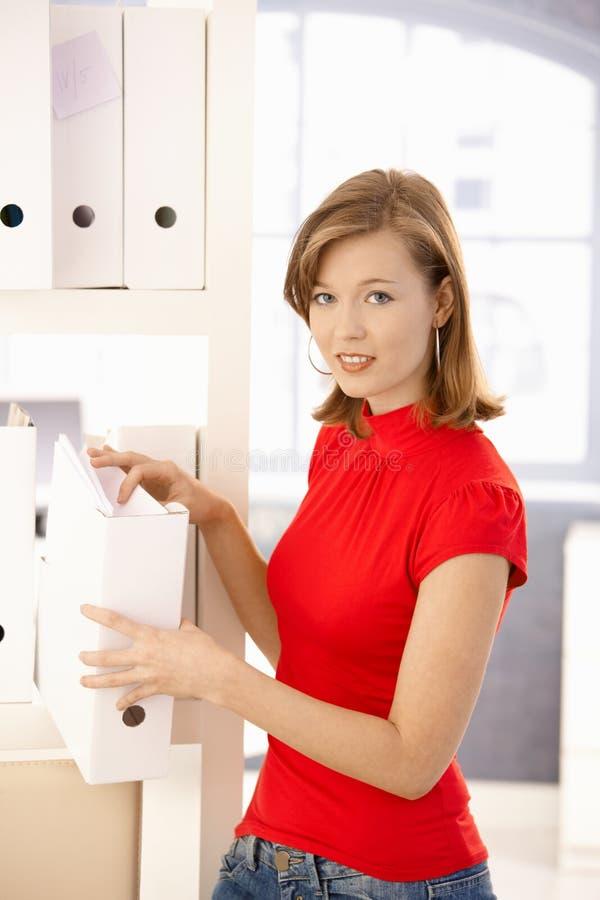 Νέος εργαζόμενος γραφείων που οργανώνει τις γραμματοθήκες στοκ φωτογραφία