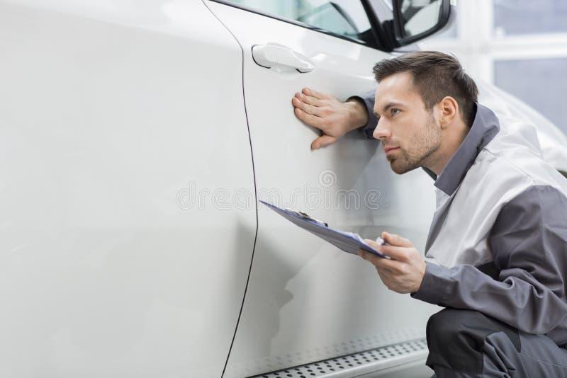 Νέος εργαζόμενος επισκευής αρσενικών που εξετάζει το αυτοκίνητο στο αυτοκινητικό κατάστημα επισκευής στοκ εικόνες