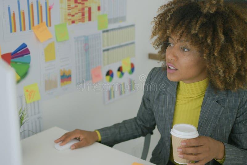 Νέος εργαζόμενος που έχει τον καφέ χρησιμοποιώντας τον υπολογιστή στοκ φωτογραφία με δικαίωμα ελεύθερης χρήσης