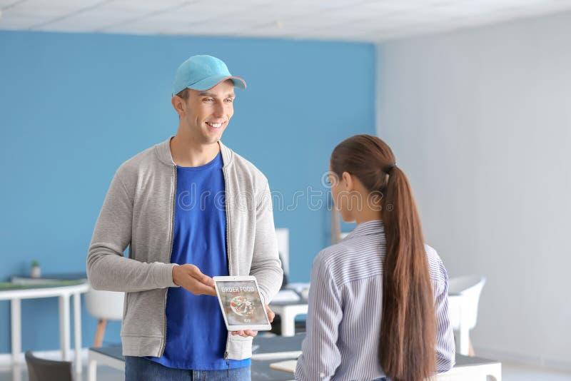 Νέος εργαζόμενος της υπηρεσίας παράδοσης τροφίμων με τον υπολογιστή ταμπλετών και του πελάτη στο εσωτερικό στοκ φωτογραφία