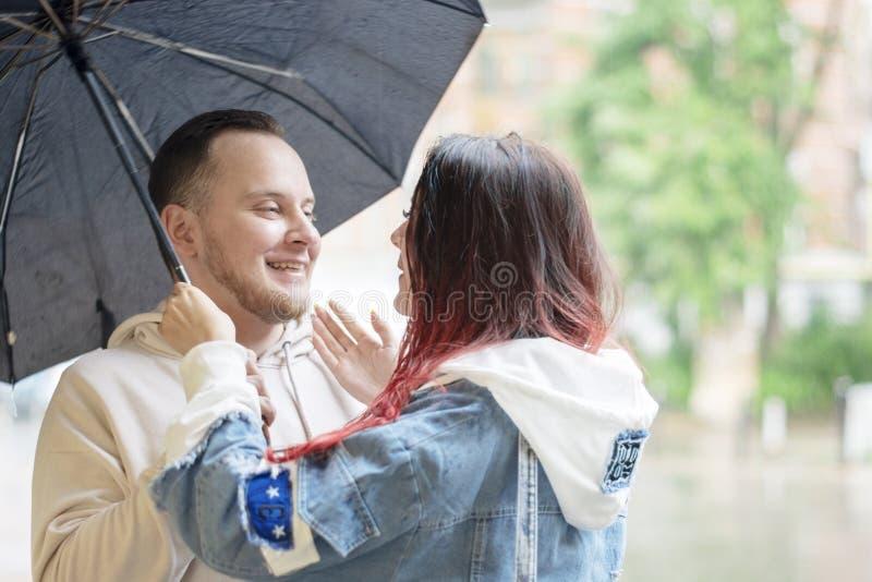 Νέος ερωτευμένος ευτυχής ζευγών κάτω από μια ομπρέλα στη βροχή το καλοκαίρι στοκ φωτογραφία με δικαίωμα ελεύθερης χρήσης