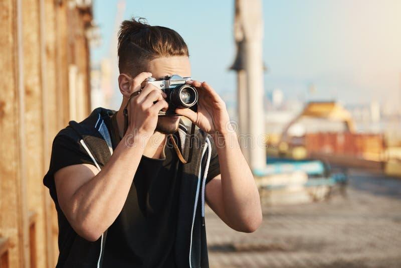 Νέος ευρωπαϊκός τύπος που στέκεται στο λιμάνι που κοιτάζει μέσω της κάμερας παίρνοντας τις εικόνες της θάλασσας ή των γιοτ, περπά στοκ εικόνες