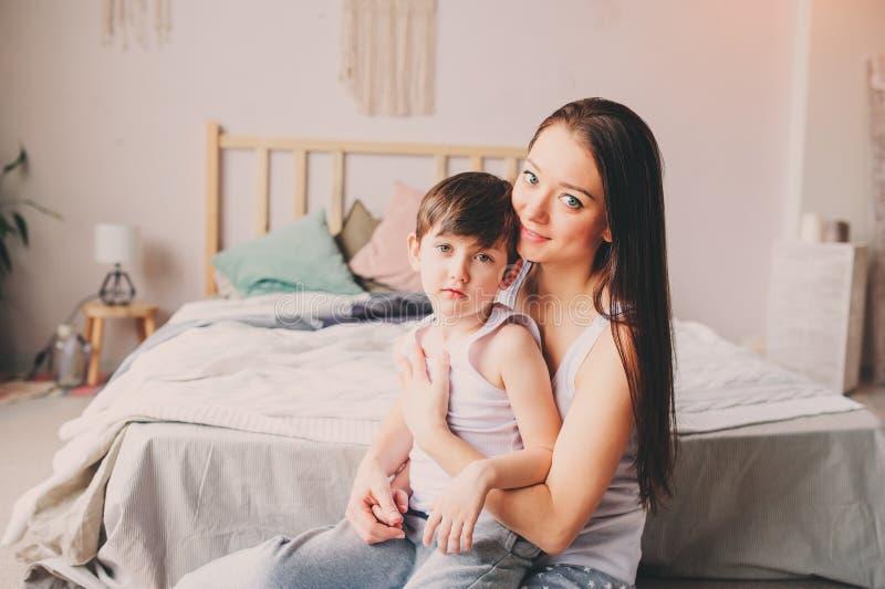 Νέος ευτυχής γιος παιδιών μητέρων ανακουφίζοντας στην κρεβατοκάμαρα στοκ φωτογραφία με δικαίωμα ελεύθερης χρήσης