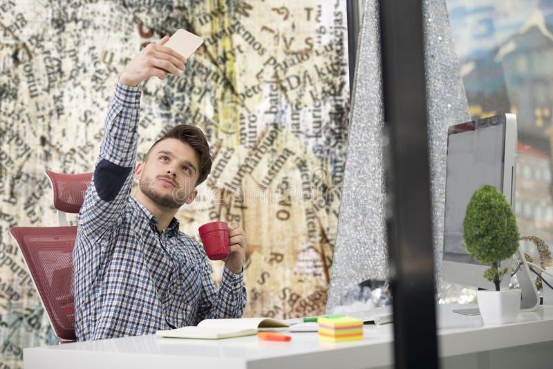 Νέος ευτυχής επιχειρηματίας που χαμογελά διαβάζοντας το smartphone του στοκ φωτογραφίες