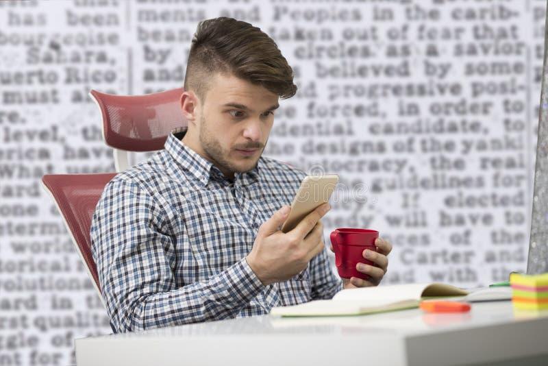 Νέος ευτυχής επιχειρηματίας που χαμογελά διαβάζοντας το smartphone του στοκ εικόνες