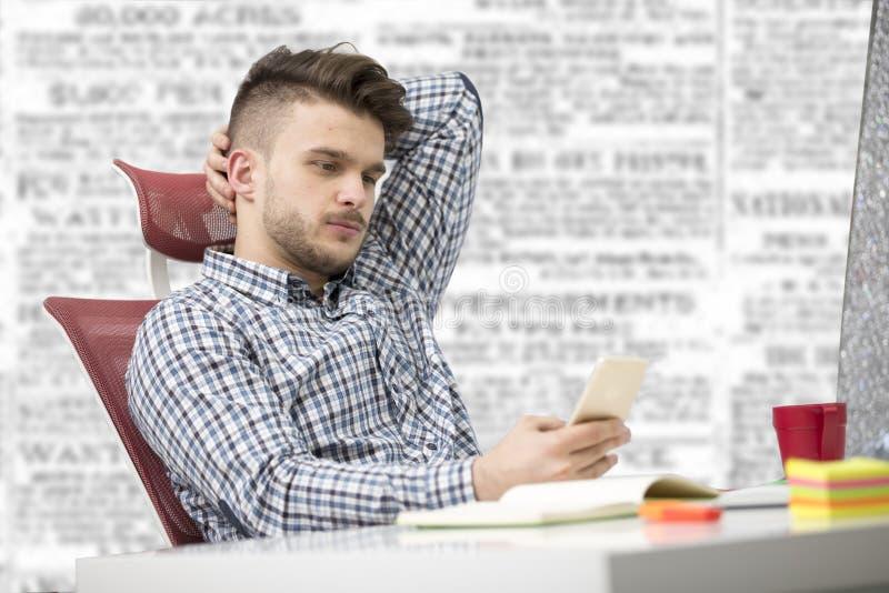 Νέος ευτυχής επιχειρηματίας που χαμογελά διαβάζοντας το smartphone του στοκ εικόνα