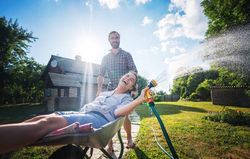 Νέος ευτυχής κήπος ποτίσματος ζευγών, ένα κορίτσι με μια μάνικα διαθέσιμη σε ένα καροτσάκι στοκ φωτογραφία με δικαίωμα ελεύθερης χρήσης