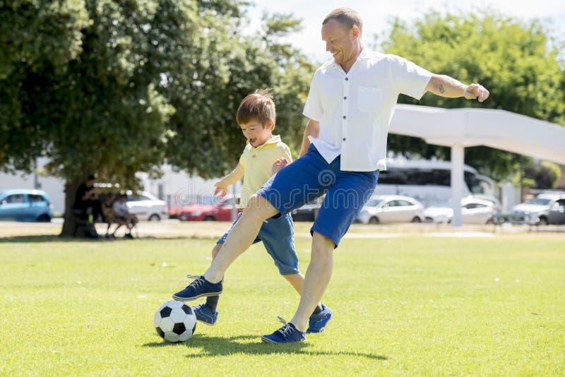 Νέος ευτυχής πατέρας και συγκινημένος λίγα χρονών γιος 7 ή 8 που παίζει μαζί το ποδόσφαιρο ποδοσφαίρου στον κήπο πάρκων πόλεων πο στοκ εικόνες με δικαίωμα ελεύθερης χρήσης