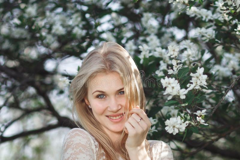Νέος εύθυμος ξανθός κήπος μήλων ανθών απόλαυσης Ανθίζοντας ελατήριο, αγάπη, έννοια ευτυχίας στοκ εικόνες με δικαίωμα ελεύθερης χρήσης