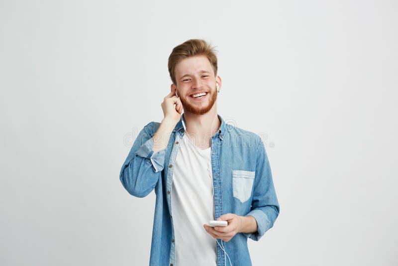 Νέος εύθυμος τύπος στα ακουστικά που χαμογελούν το τηλέφωνο εκμετάλλευσης που εξετάζει τη κάμερα που ακούει τη μουσική πέρα από τ στοκ φωτογραφία με δικαίωμα ελεύθερης χρήσης