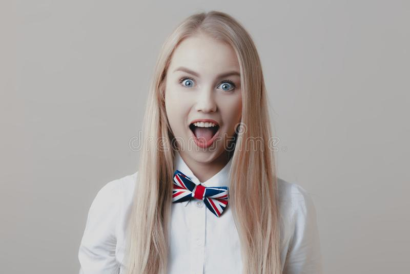 Νέος εύθυμος χαριτωμένος ξανθός με το δεσμό τόξων ανοίγει το στόμα της στο surpri στοκ εικόνες