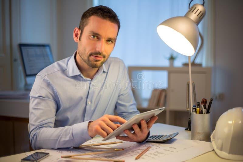 Νέος ελκυστικός αρχιτέκτονας που εργάζεται αργά στο γραφείο στοκ εικόνες με δικαίωμα ελεύθερης χρήσης