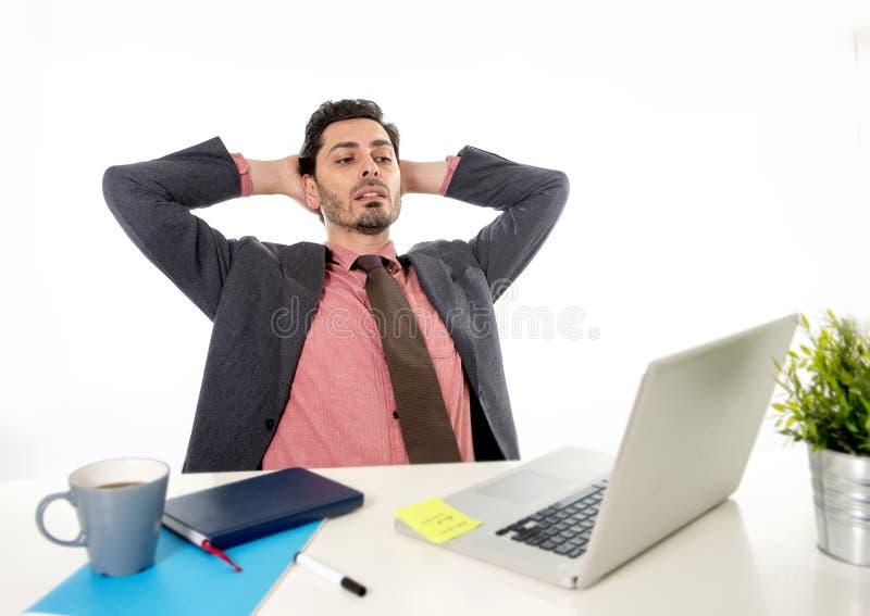 Νέος ελκυστικός λατινικός επιχειρηματίας στο κοστούμι και δεσμός που λειτουργεί στο γραφείο υπολογιστών γραφείων που κλίνει πίσω  στοκ φωτογραφία με δικαίωμα ελεύθερης χρήσης