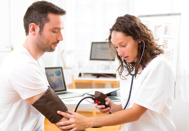 Νέος ελκυστικός γιατρός που ελέγχει τη πίεση του αίματος του ασθενή στοκ εικόνα με δικαίωμα ελεύθερης χρήσης