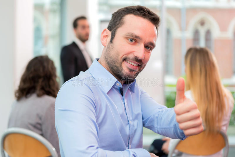 Νέος ελκυστικός επιχειρηματίας που εργάζεται στο γραφείο με το associat στοκ φωτογραφίες
