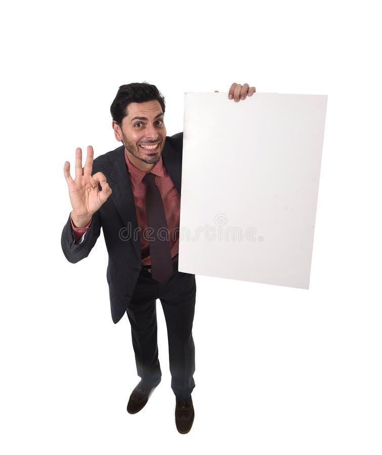 Νέος ελκυστικός επιχειρηματίας στο κοστούμι και δεσμός που κρατά και που δείχνει τον άσπρο κενό πίνακα διαφημίσεων ή που διαφημίζ στοκ εικόνες