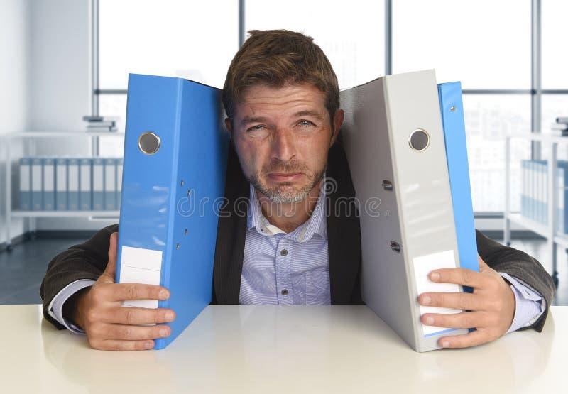 Νέος ελκυστικός πολυάσχολος επιχειρηματίας που συντρίβεται να υποστεί την τρελλή πίεση στο γραφείο που φαίνεται λυπημένο στοκ εικόνα