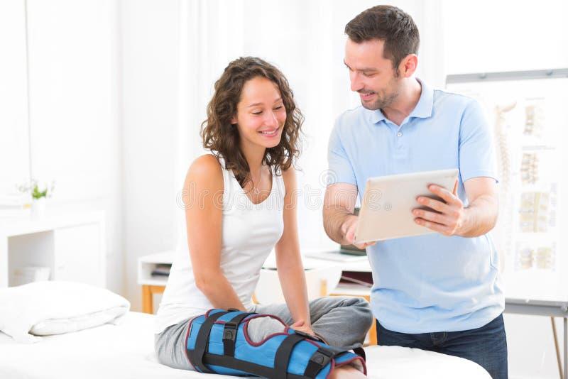 Νέος ελκυστικός φυσιοθεραπευτής που χρησιμοποιεί την ταμπλέτα με τον ασθενή στοκ εικόνες με δικαίωμα ελεύθερης χρήσης