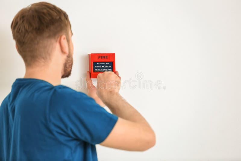 Νέος ηλεκτρολόγος που εγκαθιστά τη μονάδα συναγερμών πυρκαγιάς στον τοίχο στοκ εικόνα