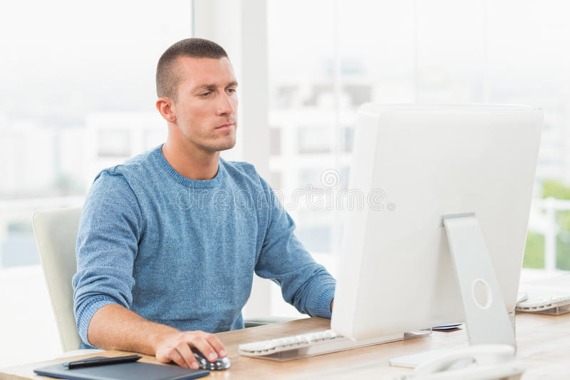 Νέος δημιουργικός επιχειρηματίας που εργάζεται στον υπολογιστή στοκ εικόνες