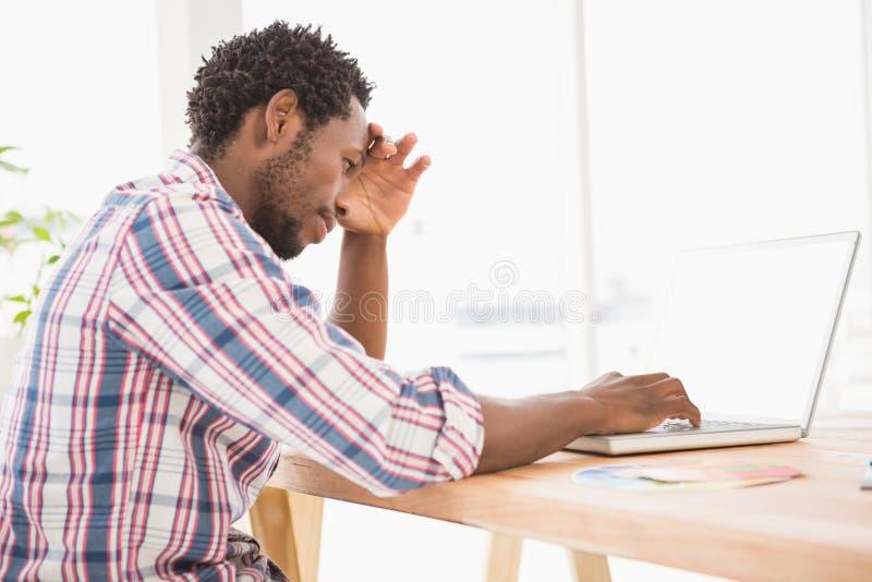 Νέος δημιουργικός επιχειρηματίας που σκέφτεται για κάτι στοκ εικόνα