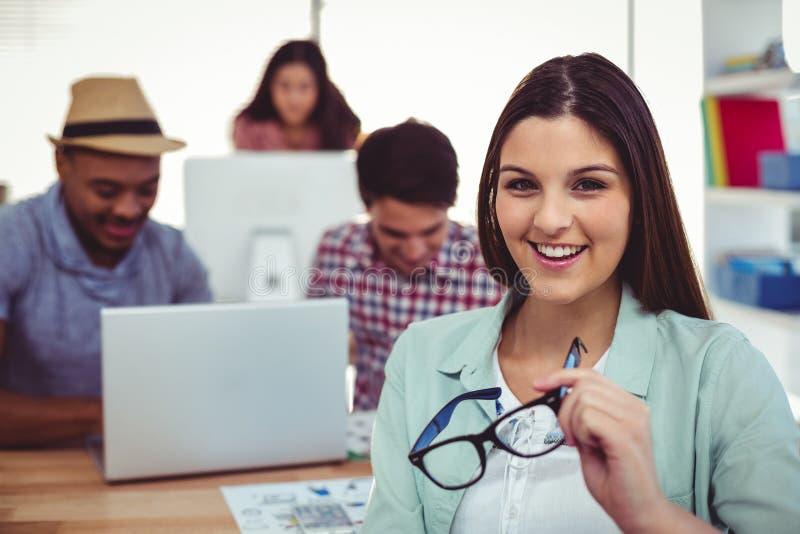 Νέος δημιουργικός εργαζόμενος που χαμογελά στη κάμερα στοκ φωτογραφία με δικαίωμα ελεύθερης χρήσης