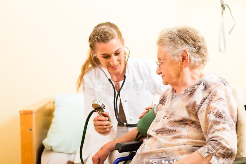 Νέος θηλυκοων πρεσβύτερος νοσοκόμων και στη ιδιωτική κλινική στοκ εικόνα