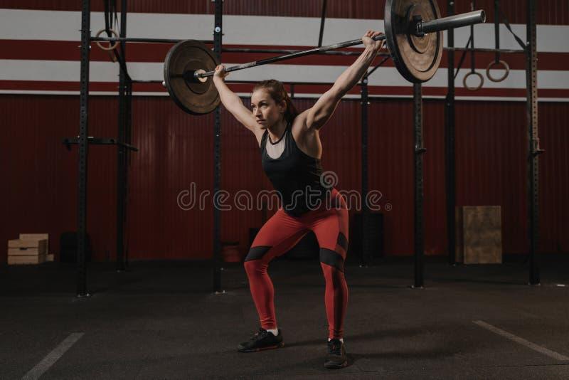 Νέος θηλυκός αθλητής crossfit που ανυψώνει τα βαριά γενικά έξοδα barbell στη γυμναστική Ισχυρή γυναίκα στοκ εικόνες με δικαίωμα ελεύθερης χρήσης