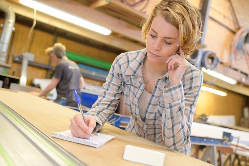 Νέος θηλυκός ξυλουργός που γράφει στο έγγραφο στο εργαστήριο στοκ εικόνα