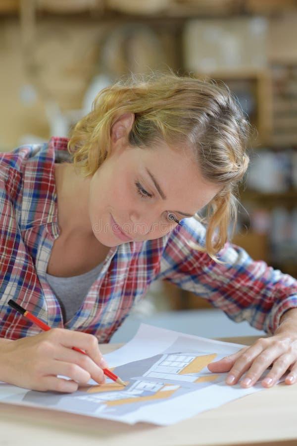 Νέος θηλυκός ξυλουργός που γράφει στο έγγραφο στο εργαστήριο στοκ φωτογραφία