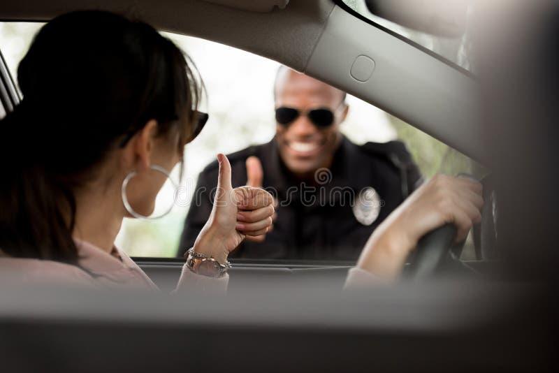 Νέος θηλυκός οδηγός στο αυτοκίνητο και χαμογελώντας αστυνομικός στοκ φωτογραφία με δικαίωμα ελεύθερης χρήσης