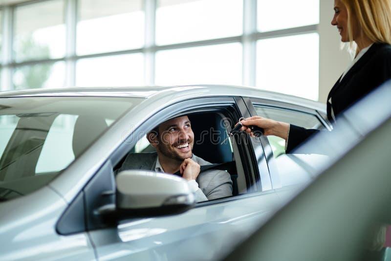 Νέος θηλυκός σύμβουλος πωλήσεων αυτοκινήτων που εργάζεται στην αίθουσα εκθέσεως στοκ εικόνα