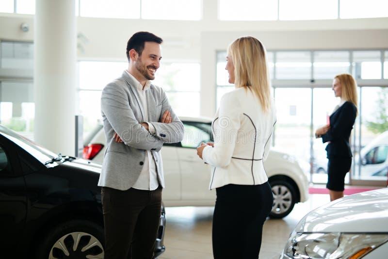 Νέος θηλυκός σύμβουλος πωλήσεων αυτοκινήτων που εργάζεται στην αίθουσα εκθέσεως στοκ φωτογραφία με δικαίωμα ελεύθερης χρήσης