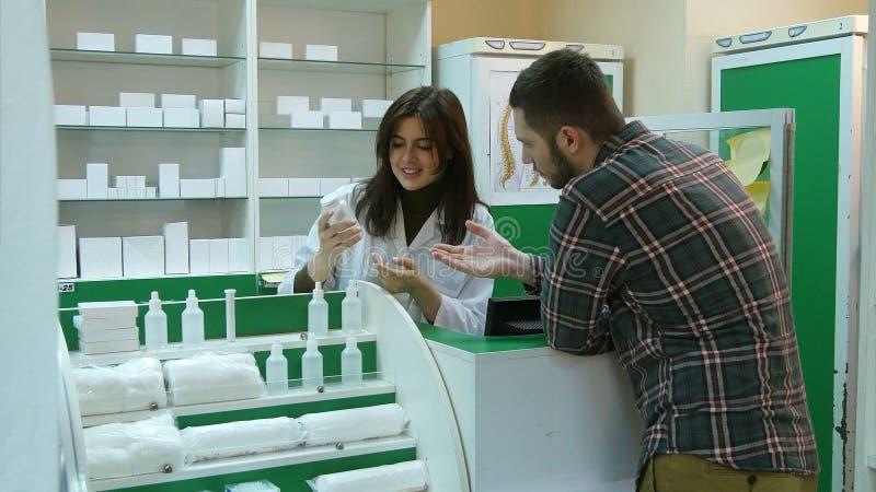 Νέος θηλυκός φαρμακοποιός που ο αρσενικός πελάτης για να αγοράσει την ταμπλέτα στο φαρμακείο στοκ εικόνες