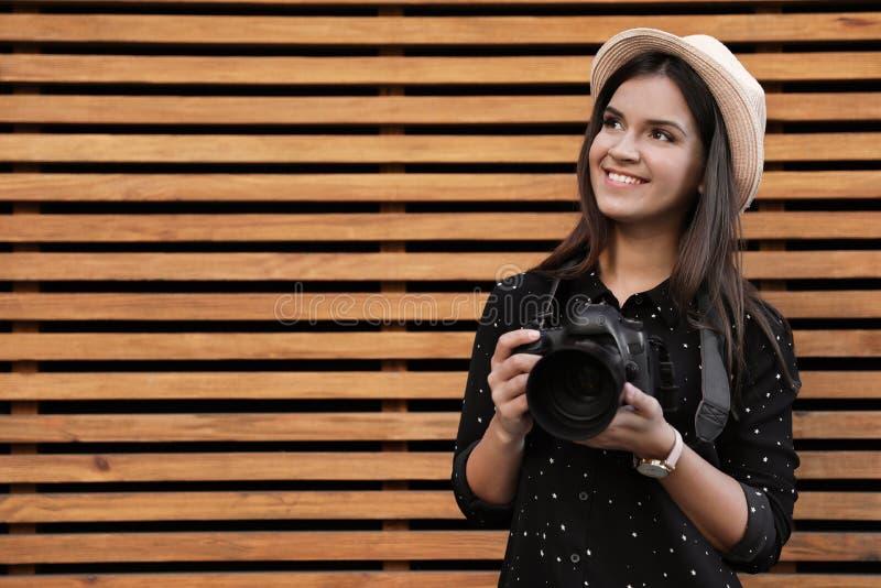 Νέος θηλυκός φωτογράφος με την επαγγελματική κάμερα κοντά στον ξύλινο τοίχο στοκ φωτογραφίες