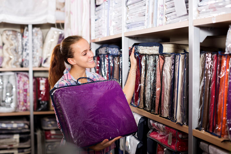 Νέος θηλυκός αγοραστής που ψάχνει για τα κλινοσκεπάσματα στοκ εικόνα